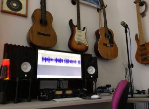 A studio with acoustic and electric guitars on the wall